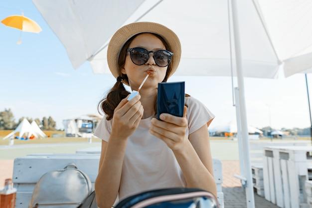 Jovem adolescente usa brilho labial.