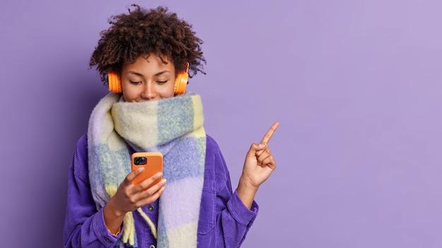 Jovem adorável adolescente com cabelo encaracolado segurando celular verifica playlsit escolhe música para ouvir indica no canto superior direito usa lenço para o dia frio de inverno mostra cópia espaço na parede roxa