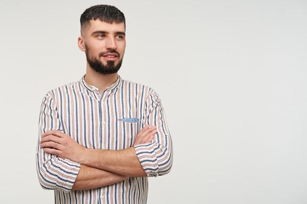 Jovem adorável cara de cabelos escuros com barba cruzando as mãos enquanto olha pensativamente para o lado e sorri ligeiramente, posando sobre uma parede branca