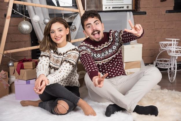 Jovem adorável casal sorridente, sentado no chão e posando.