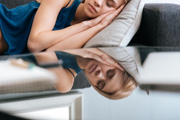 Jovem adorável exausta deitado e dormindo em casa
