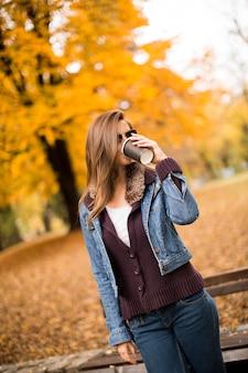 Jovem adorável feliz bebendo café ao ar livre no parque outono
