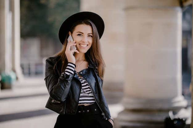 Jovem adorável garota de cabelos castanhos em uma jaqueta de couro e chapéu preto no calçadão da cidade conversando por telefone