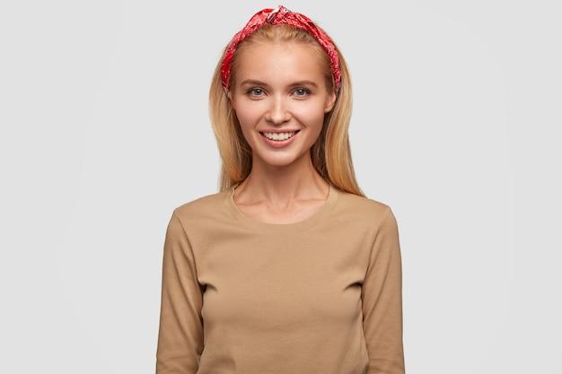 Jovem adorável loira sorridente, cabelo comprido, usa bandana e suéter casual bege, expressa emoções positivas