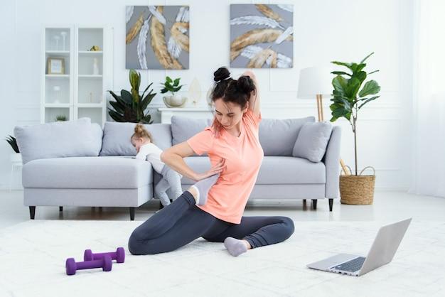 Jovem adorável mãe fazendo exercícios de alongamento e praticando ioga com a menina em casa. conceito de saúde e esportes.