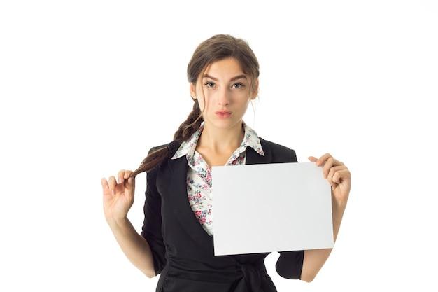 Jovem adorável morena de negócios de uniforme com um cartaz branco nas mãos, isolado na parede branca