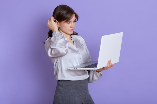 Jovem adorável mulher concentrada usando laptop contra a parede lilás, estando ocupada, olha para a tela do computador portátil, tocando seu cabelo enquanto pensa em seu trabalho, pensativa empresária trabalhando.