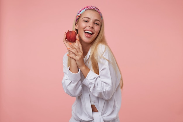 Jovem adorável mulher loira com manicure laranja em uma camisa branca olhando e segurando um pêssego perto da bochecha, sendo positiva e feliz, isolada