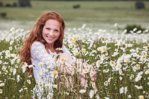 Jovem adorável mulher sorridente maravilha-se na flor, rasgando pétalas