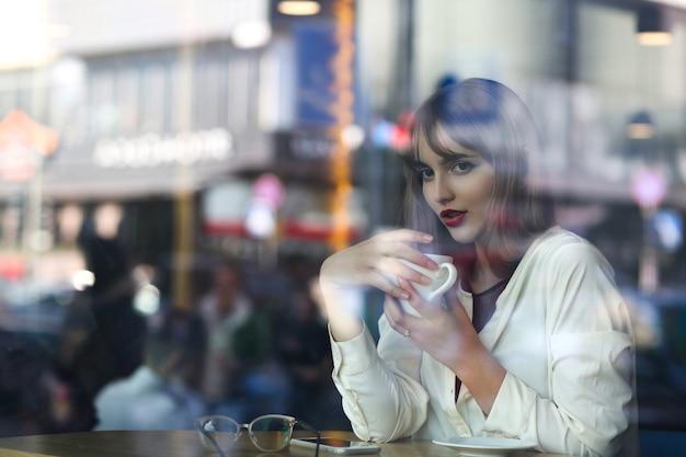 Jovem adorável passando um tempo no restaurante com uma xícara de café, vista através do vidro