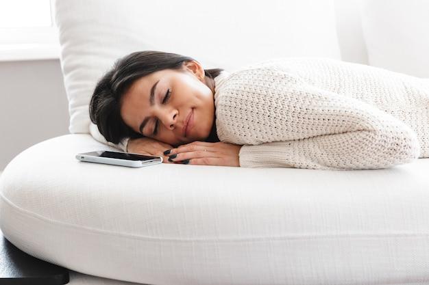 Jovem adorável relaxando em um sofá em casa, dormindo com um telefone celular