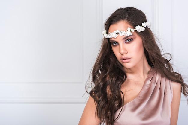 Jovem adorável senhora de vestido com coroa de flores na cabeça