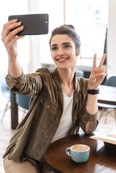 Jovem adorável tirando uma selfie enquanto está sentado dentro de casa tomando café