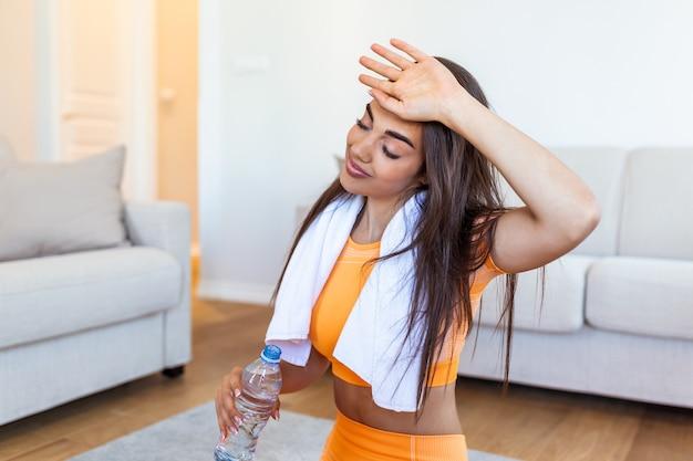 Jovem adulta bebendo água de uma garrafa plástica, sentada na esteira de fitness e descansando após o treino em casa.