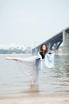 Jovem adulta branca mulher numa praia fazendo arabesco na água,