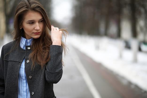 Jovem adulta com casaco na rua na cidade