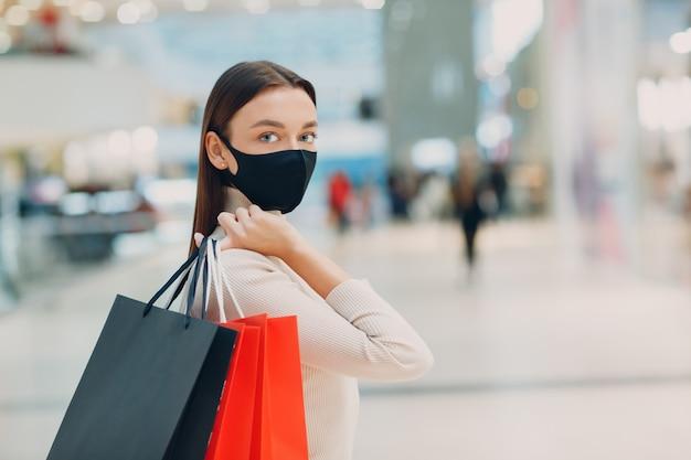 Jovem adulta com máscara protetora médica carregando sacolas de papel nas mãos no supermercado