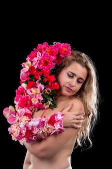 Jovem adulta com o braço coberto de flores, simbolizando o conceito da mãe terra sobre um negro.