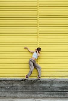 Jovem adulta de blusa branca e calça cinza dançando na frente de uma parede amarela brilhante