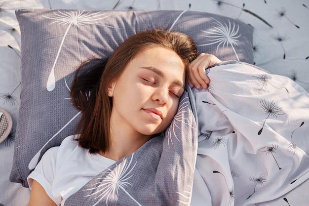Jovem adulta de cabelos escuros com os olhos fechados deitada em um travesseiro macio sob o cobertor e descansando