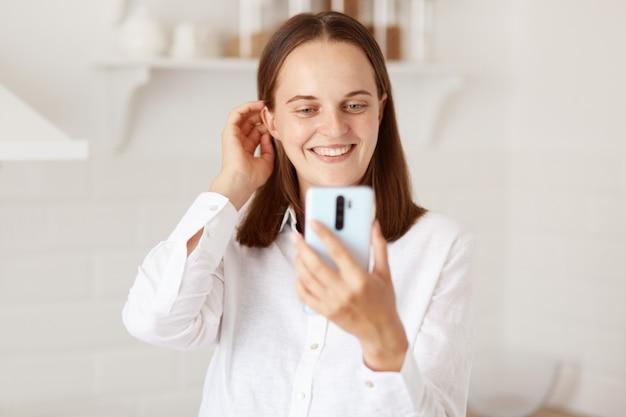 Jovem adulta de cabelos escuros feliz mulher usando smartphone para fazer selfie, posando na cozinha em casa, tendo uma conversa agradável via videochamada e sorrindo.