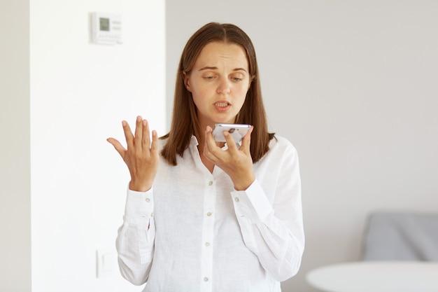 Jovem adulta de cabelos escuros, vestindo camisa branca estilo casual, gravando mensagem de voz, tendo uma conversa desagradável, em pé com o braço estendido em uma sala iluminada em casa.