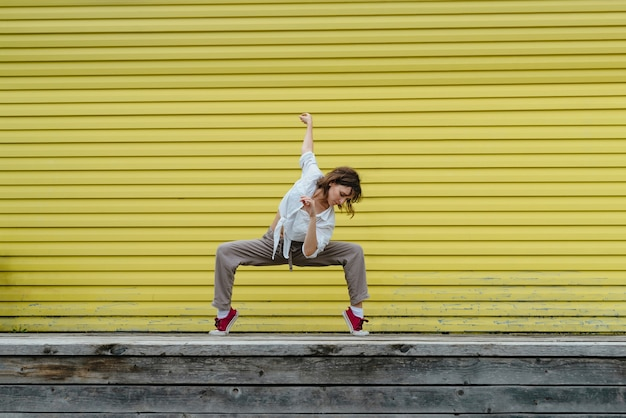 Jovem adulta de camisa branca e calça de linho cinza dançando em frente a uma parede amarela brilhante, foco seletivo