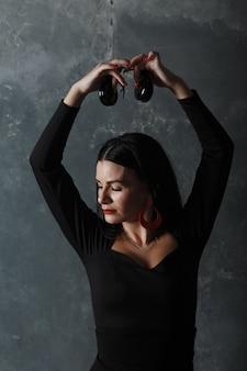 Jovem adulta espanhola dançando flamenco com castanholas na parede cinza vintage