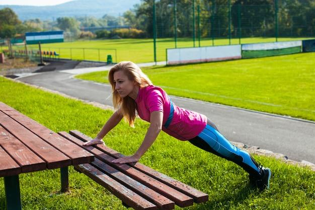 Jovem adulta está fazendo exercícios de ginástica ao ar livre. vida livre saudável e desportiva