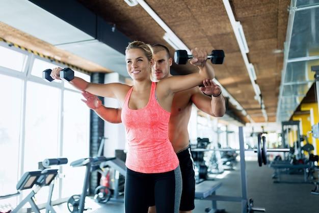 Jovem adulta fazendo exercícios para os ombros na academia com o treinador