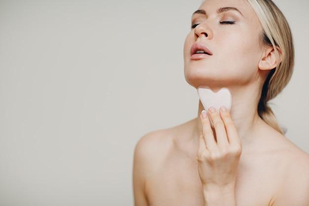 Jovem adulta fazendo massagem facial com guasha