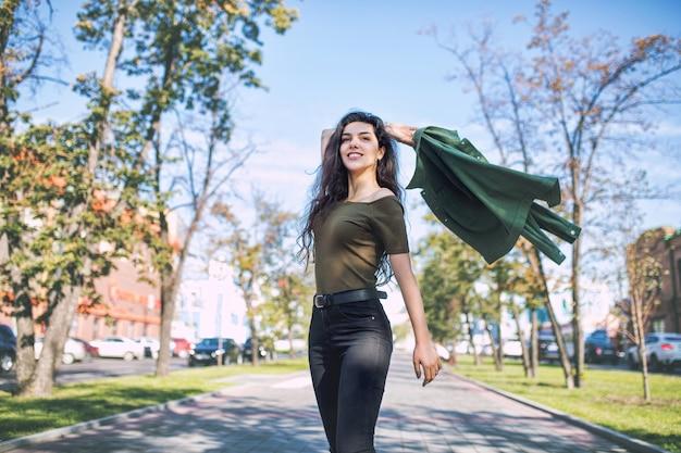 Jovem adulta linda morena com roupas casuais feliz andando pela cidade