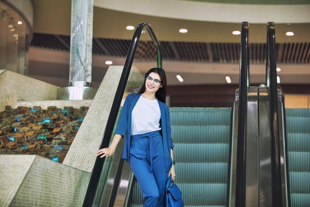 Jovem adulta linda morena na escada rolante no centro de negócios