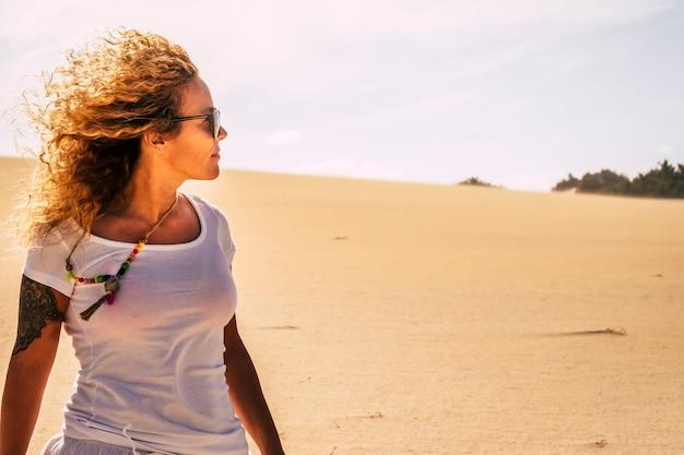Jovem adulta loira bonita com cabelo comprido encaracolado desfrutando de liberdade e independência em atividades de lazer ao ar livre com areia do deserto