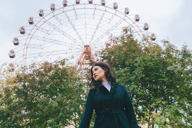 Jovem adulta mulher asiática com um casaco escuro na frente da roda gigante ao ar livre