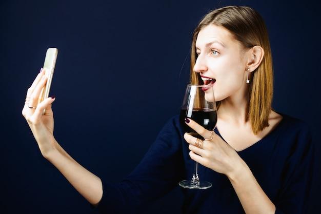 Jovem adulta mulher branca com batom de ameixa escuro, segurando um copo de vinho tinto e fazendo selfie