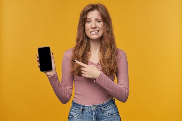 Jovem adulta mulher ruiva, com penteado ondulado confuso expressão facial, aponta com um dedo para a tela em branco de seu telefone