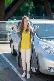 Jovem adulta perto de um carro com chaves