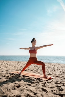 Jovem adulta praticando ioga na praia, pose de virabhadrasana ii, foco seletivo