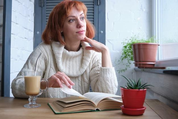 Jovem adulta ruiva relaxando em casa com uma bebida quente e um livro