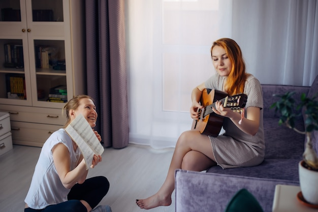 Jovem adulta segura o caderno de música e olha para a amiga tocando violão. duas lindas garotas tocam música em casa. amizade, amor, lazer familiar, hobbies.