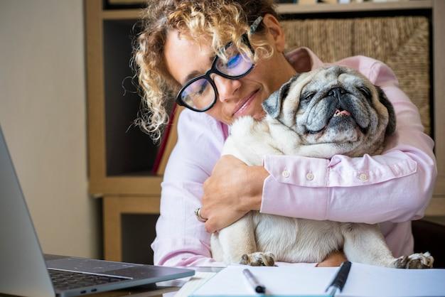 Jovem adulta trabalhando em um laptop e abraçando seu adorável cachorro Foto Premium
