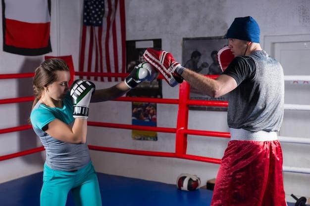 Jovem adulta treinando kickboxing com seu treinador em um ringue de boxe normal em uma academia