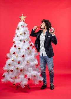 Jovem adulto animado segurando o relógio, bebendo uma taça de vinho e perto da árvore de natal na foto vermelha