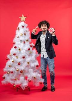 Jovem adulto animado segurando o relógio, erguendo uma taça de vinho e perto da árvore de natal na foto vermelha.