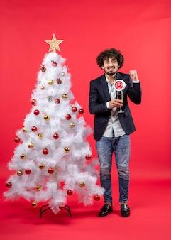 Jovem adulto animado segurando um relógio e uma taça de vinho e perto da árvore de natal na foto vermelha