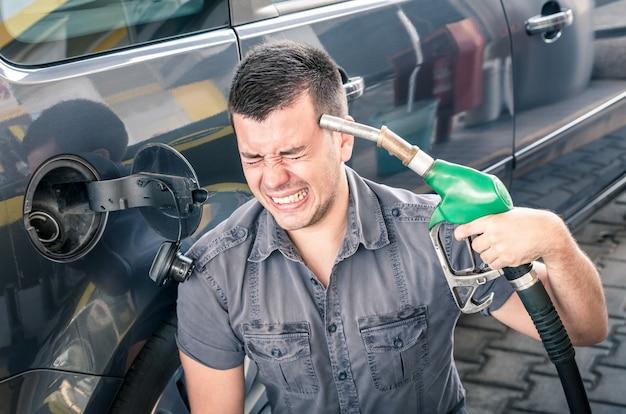 Jovem adulto atirando em si mesmo sobre preços loucos de gasolina e combustível.