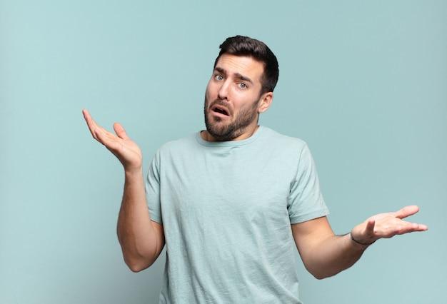 Jovem adulto bonito encolhendo os ombros com uma expressão estúpida, maluca, confusa e perplexa, sentindo-se irritado e sem noção