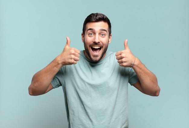 Jovem adulto bonito sorrindo, parecendo feliz, positivo, confiante e bem-sucedido, com os dois polegares para cima