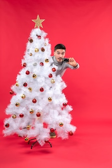 Jovem adulto chocado com uma blusa cinza em pé atrás da árvore de natal decorada e olhando para o telefone vermelho